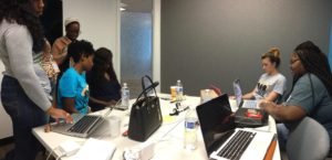6 members of the TeenSquad team in meeting room working on application.